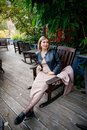 Beautiful young pregnant woman wearing dress and leather shirt resting in city park cafe, stylish pregnancy shot. Beautiful woman Royalty Free Stock Photo