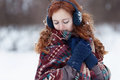 Beautiful young red-haired woman in blue headphones and gloves. Royalty Free Stock Photo