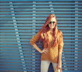 Beautiful young red-haired young girl in sunglasses standing near the wall of blue wooden planks summer warm day Royalty Free Stock Photo