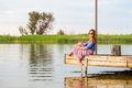 Beautiful young red woman sitting on a wooden pier in a colorful long sarafan dress and putting her leg in a water Royalty Free Stock Photo