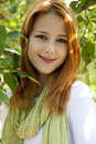 Beautiful young redhead woman near the apple tree Royalty Free Stock Photo
