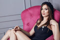Beautiful young sexy brunette woman in black beret and a short silk dress smokes a cigarette sitting in pink armchair stylish clot Royalty Free Stock Photo