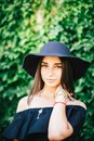 Beautiful young sexy girl with swarthy skin and brunette with black hair dressed in a stylish black dress and hat on background of Royalty Free Stock Photo