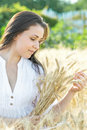 Beautiful young sexy woman holding wheat ears at summer sunny day. Portrait of pretty girl outdoor Royalty Free Stock Photo