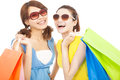 Beautiful young sisters holding shopping bags over white background Royalty Free Stock Photos