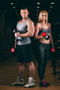 Beautiful young sporty sexy couple showing muscle and workout in gym dumbbell Royalty Free Stock Photo