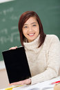 Beautiful young student displaying her tablet asian sitting in class computer holding the blank screen towards the camera with a Royalty Free Stock Photography