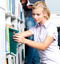 Beautiful Young student taking book from shelf Stock Photo