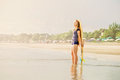 Beautiful young surfer girl stays on the beach at sunset light with yellow surfboard healthy lifestyle leisure travel holiday and Stock Photography
