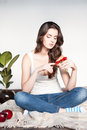 Beautiful young thoughtful casual brunette woman sitting wool plaid holding red flower Royalty Free Stock Photography