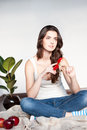 Beautiful young thoughtful casual brunette woman sitting wool plaid holding red flower Stock Photography