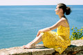 Beautiful young woman admiring the sea sitting on a parapet and Royalty Free Stock Photo