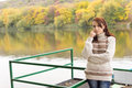 Beautiful young woman alongside a river standing leaning against metal railings tranquil lake or enjoying the peace and quiet of Royalty Free Stock Photography