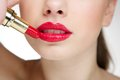 Beautiful young woman applying red lipstick Royalty Free Stock Photo