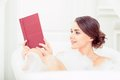 Beautiful young woman in bath with a book Royalty Free Stock Photo