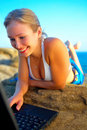Beautiful Young Woman on the Beach with Laptop Royalty Free Stock Photo
