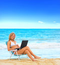 Beautiful Young Woman on the Beach with Laptop Stock Photography
