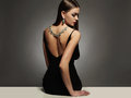 Beautiful young woman.beauty sitting girl Girl with a necklace on her back Royalty Free Stock Photo