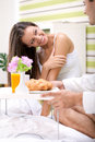 Beautiful young woman in bed with her husband serving breakfast women looking thanks for Stock Photo