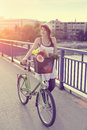Beautiful young woman with bicycle crossing the bridge her that has flowers in basket Royalty Free Stock Photo