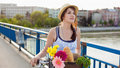 Beautiful young woman with bicycle crossing the bridge her that has flowers in basket Royalty Free Stock Photography