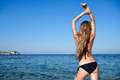 Beautiful young woman in bikini on the sunny beach standing water Stock Image