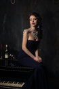 Beautiful young woman in black dress next to a piano with candelabra candles and wine, dark dramatic atmosphere of the castle. Royalty Free Stock Photo