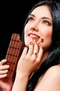 Beautiful young woman with black hair holding a chocolate bar Royalty Free Stock Images