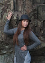 Beautiful young woman in black hat at the rock with long hair Royalty Free Stock Photo