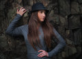 Beautiful young woman in black hat at the rock with long hair Stock Image