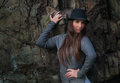 Beautiful young woman in black hat at the rock with long hair Stock Photo
