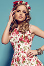Beautiful young woman with blond curly hair wears elegant clothes and bijou fashion studio photo of flower s headband Royalty Free Stock Photos