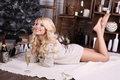 Beautiful young woman with blond hair and charming smile wears cozy knitted cardigan posing beside christmas tree and presents Royalty Free Stock Image