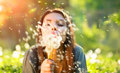Beautiful young woman blowing dandelions Royalty Free Stock Photo
