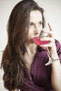 Beautiful young woman with brown hair and eyes holding a pink martini Royalty Free Stock Images