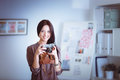 Beautiful young woman with camera standing near desl in office