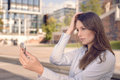 Beautiful young woman checking her appearance in a small handheld mirror in the street as she holds long brown hair away from Royalty Free Stock Images