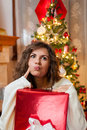 Beautiful young woman at christmas portrait of smiling with a gift box not satisfied with her gifts over living room Stock Image