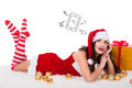 Beautiful young woman in Christmas wear dreaming about tablet PC as gift. Isolated on white background.