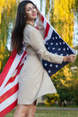 Beautiful young woman with classic dress holding american flag in the park fashion model holding us smiling and looking at camera Stock Photography