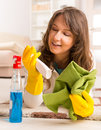 Beautiful young woman cleaning her house laying on the floor after wearing yellow gloves with spray cleaners and cloth Royalty Free Stock Photos