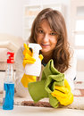 Beautiful young woman cleaning her house laying on the floor after wearing yellow gloves with spray cleaners and cloth Stock Photos