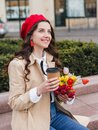 Beautiful young woman with coffee to go and spring tulips flowers bouquet at city street. Happy girl walking outdoors. Spring Royalty Free Stock Photo