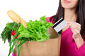 Beautiful young woman with credit card holding paper bag with groceries. Isolated. Shopping and groceries concept. Royalty Free Stock Photo