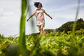 Beautiful young woman dancing in the green grass field Royalty Free Stock Photo