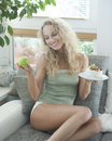 Beautiful young woman deciding between cake and apple while sitting on sofa