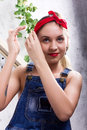 Beautiful young woman in denim overalls and a bandana looking at the camera as the mirror, Chupa Chups licking and Royalty Free Stock Photo