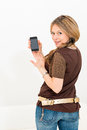Beautiful young woman displaying mobile phone on white background Royalty Free Stock Images
