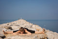 Beautiful young woman doing yoga on the beach in hanuman posture practicing rocks Royalty Free Stock Image
