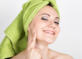 Beautiful Young woman dressed in a bath towel makes a cosmetic mask on the face. beauty industry and home skin care Royalty Free Stock Photo